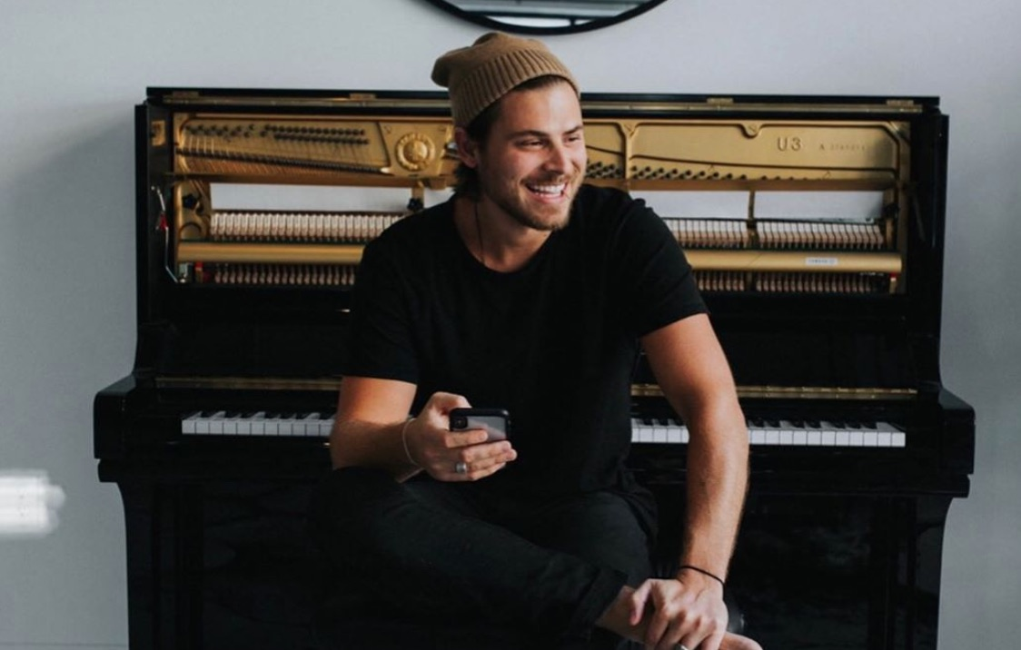Cory Asbury smiling and sitting in front of a piano with a brown beanie on his head, black t-shirt and a cell phone in hand